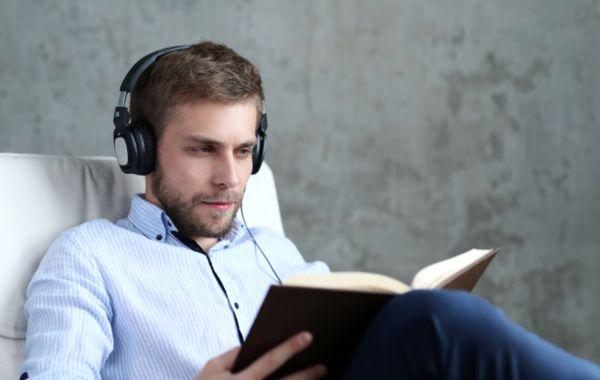Молодой человек слушает подкаст во время чтения книги
