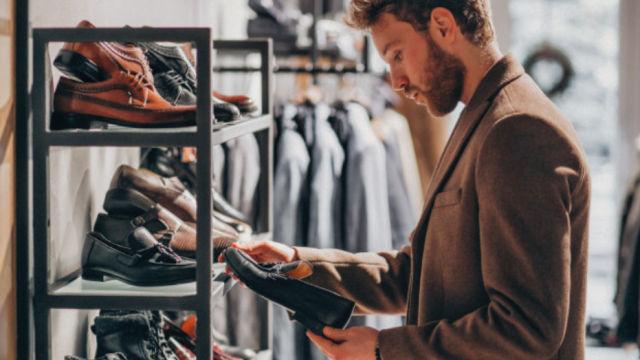 Мужчина размышляет о покупке обуви в магазине