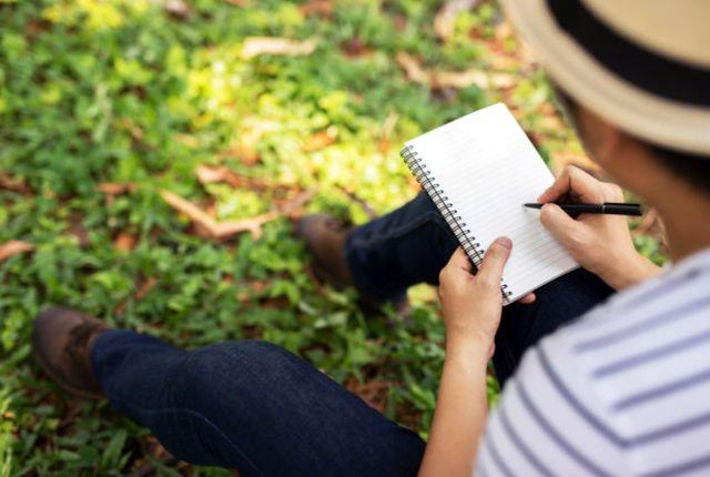 Молодой человек в парке заполняет карманный блокнот