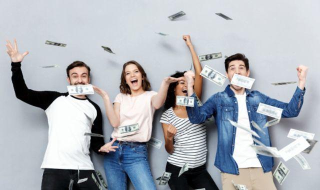 Группа молодых людей радуется потоку денег