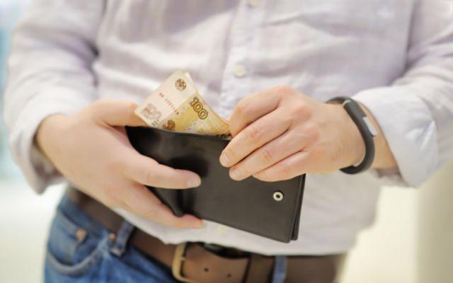 Мужчина достаёт из кошелька пару купюр по 100 рублей