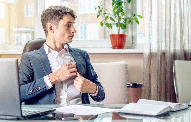 Мужчина за офисным столом прячет кредитную карту в карман пиджака