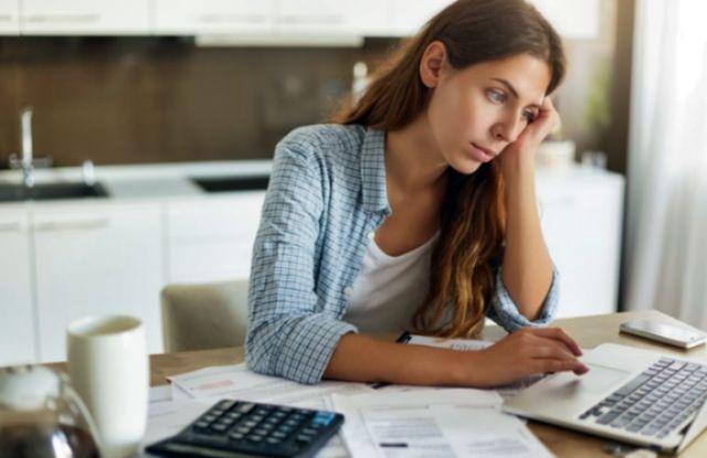 Молодая женщина за ноутбуков ищет решение со своими кредитными долгами
