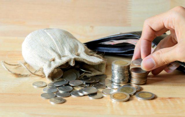 Монеты из мешочка рассыпанные по столу и кошелёк с деньгами