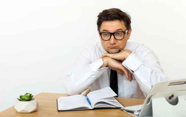 Мужчина на работе скучает из-за отсутствия рабочих задач