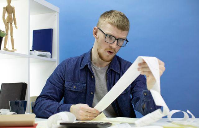 Молодой человек изучает квитанции и составляет личный бюджет