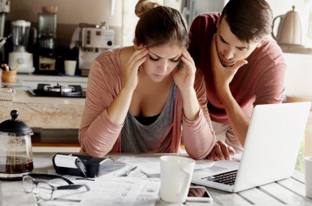 Молодая семейная пара изучает счета, чтобы найти выход из долговой ямы