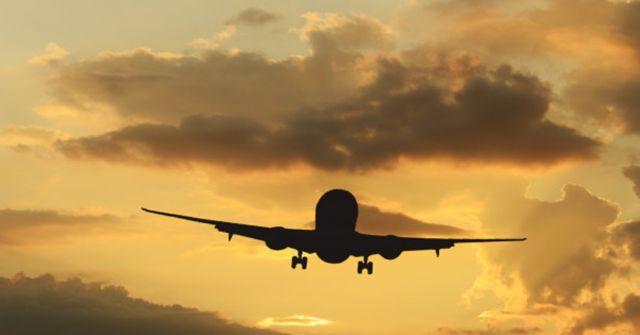 Взлет самолета на фоне красочного неба во время заката солнца
