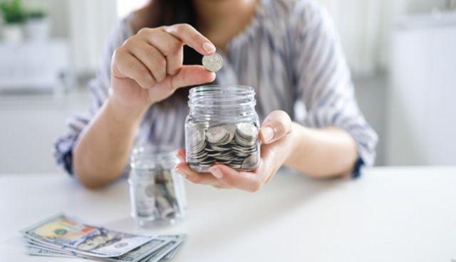 Женщина бросает монетку в банку с накоплениями